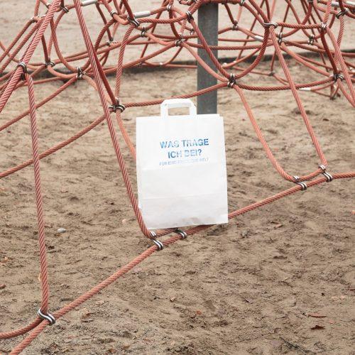 Eine weiße Papiertüte bedruckt mit der Frage Was trage ich bei? Für eine friedliche Welt. Die Tüte steht auf einem Kletternetz auf einem Spielplatz.