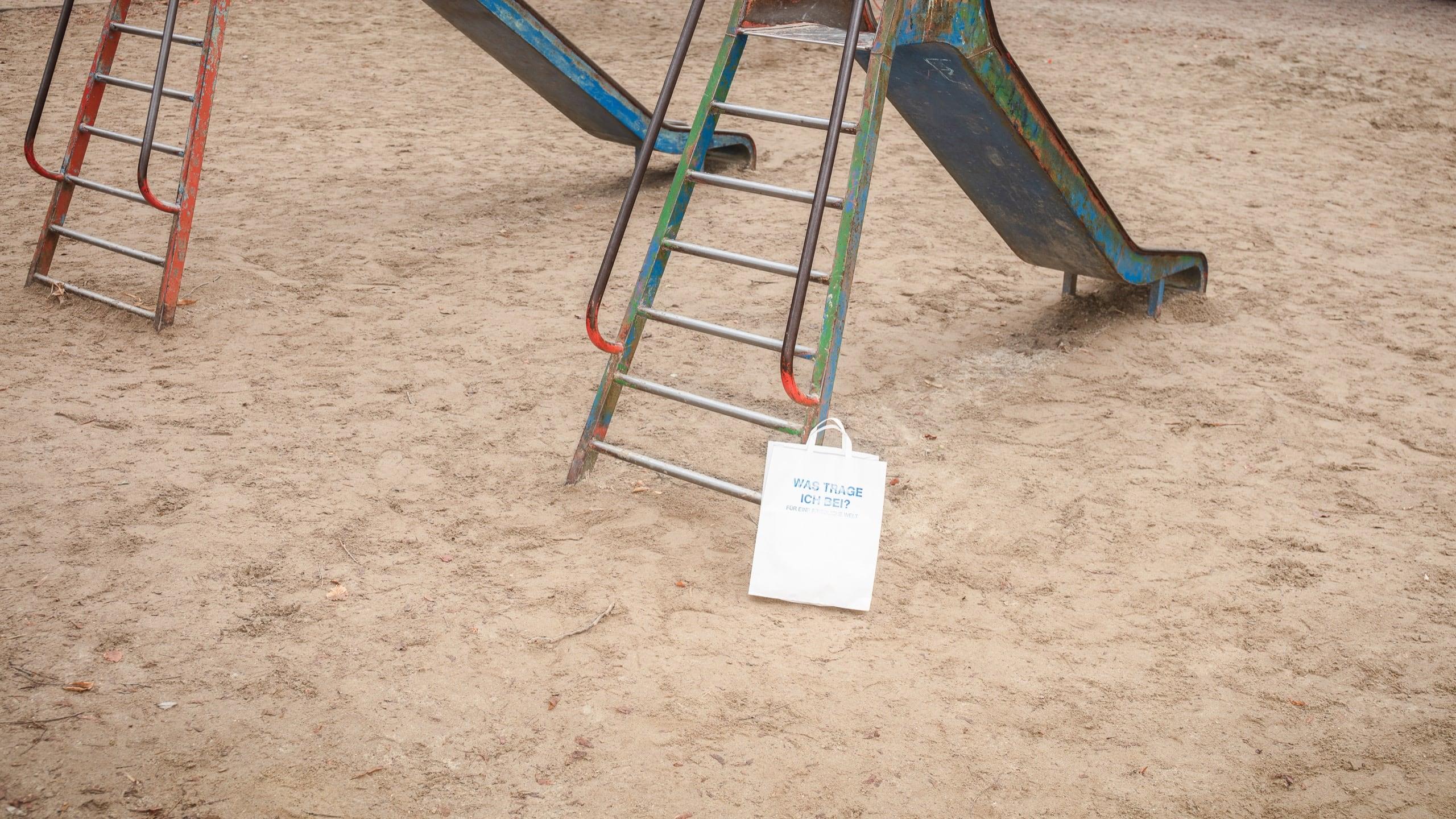 Eine weiße Papiertüte bedruckt mit der Frage Was trage ich bei? Für eine friedliche Welt. Die Tüte steht angelehnt an eine grün rote Rutsche auf einem Spielplatz.