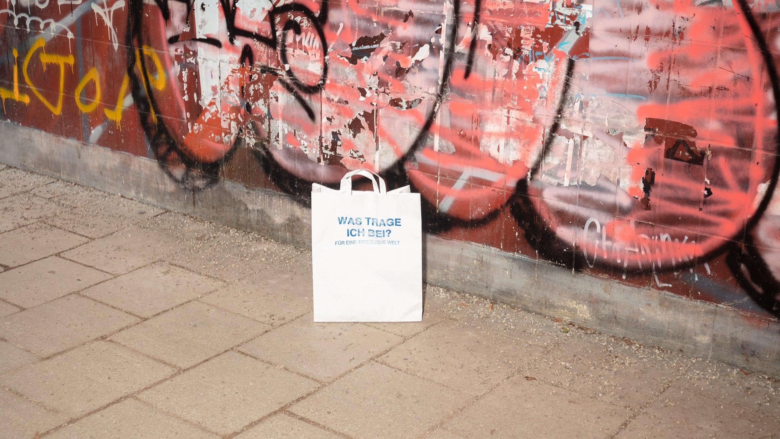 Eine weiße Papiertüte bedruckt mit der Frage Was trage ich bei? Für eine friedliche Welt. Die Tüte steht mittig vor einer Wand mit roten Graffitis.