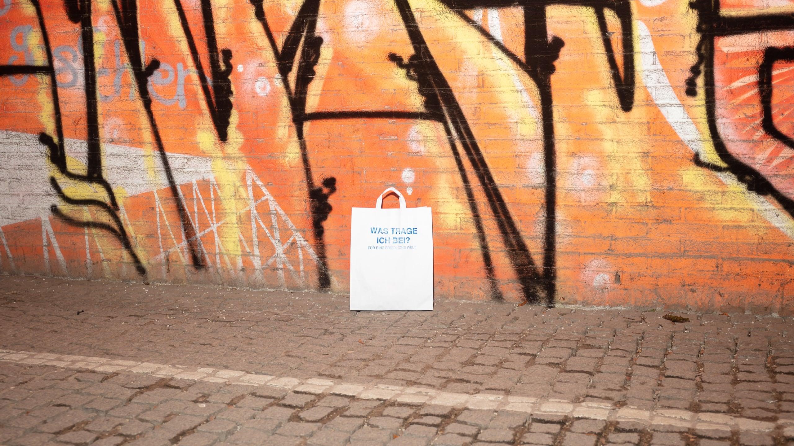 Eine weiße Papiertüte bedruckt mit der Frage Was trage ich bei? Für eine friedliche Welt. Die Tüte steht mittig vor einer Wand mit orangefarbenen Graffitis.