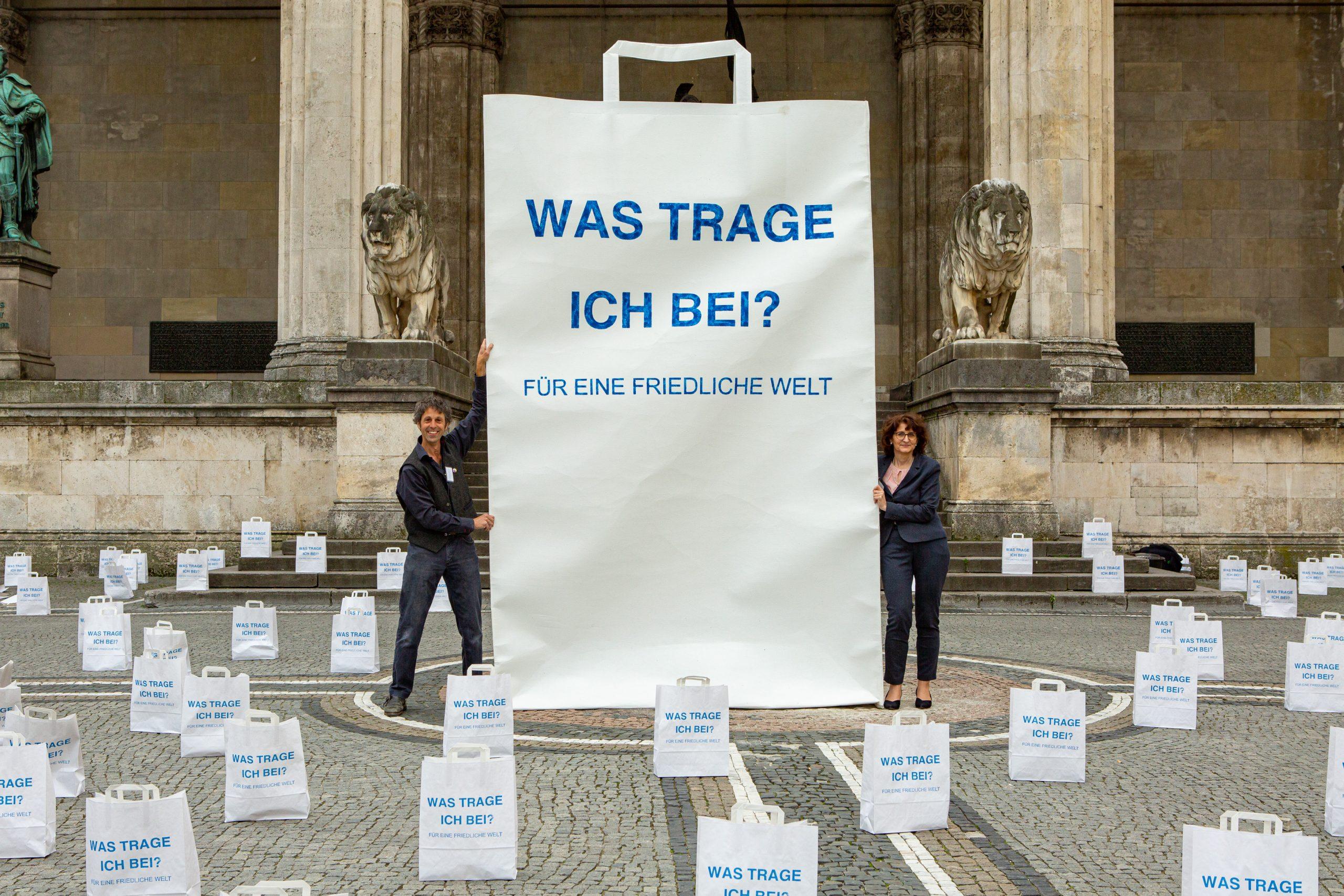 Die Kunstinstallation des Projekts Frieden Leben. Eine große Papiertüte in einem Meer aus kleinen Papiertütenallesamt bedruckt mit der Frage Was trage ich bei? Für eine friedliche Welt. Links und rechts ein Mann und eine Frau.