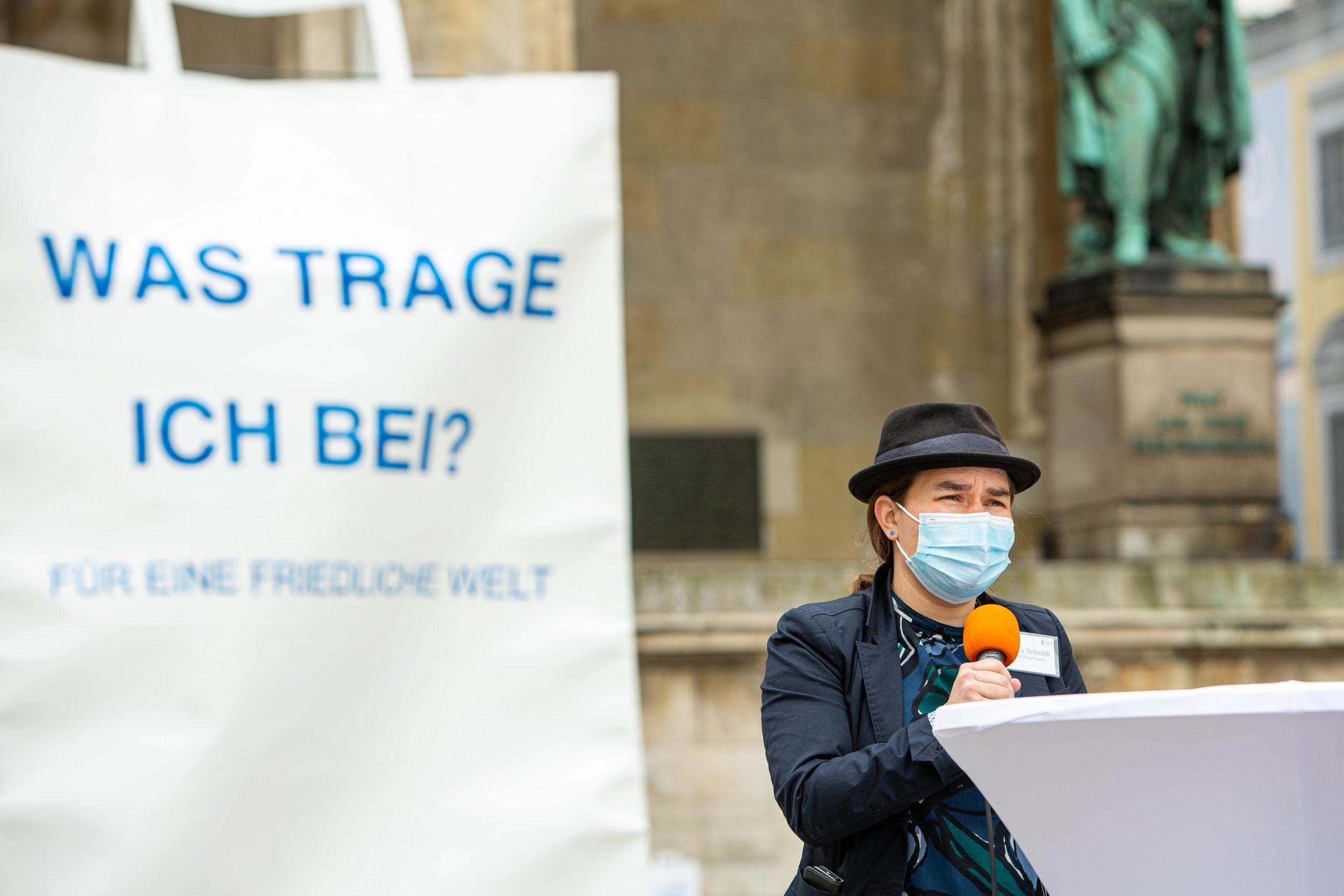 Im Hintergrund eine riesige Papiertüte bedruckt mit der Frage Was trage ich bei? Für eine friedliche Welt. Im Vordergrund eine Frau mit Hut und Mikrofon an einem Stehtisch.