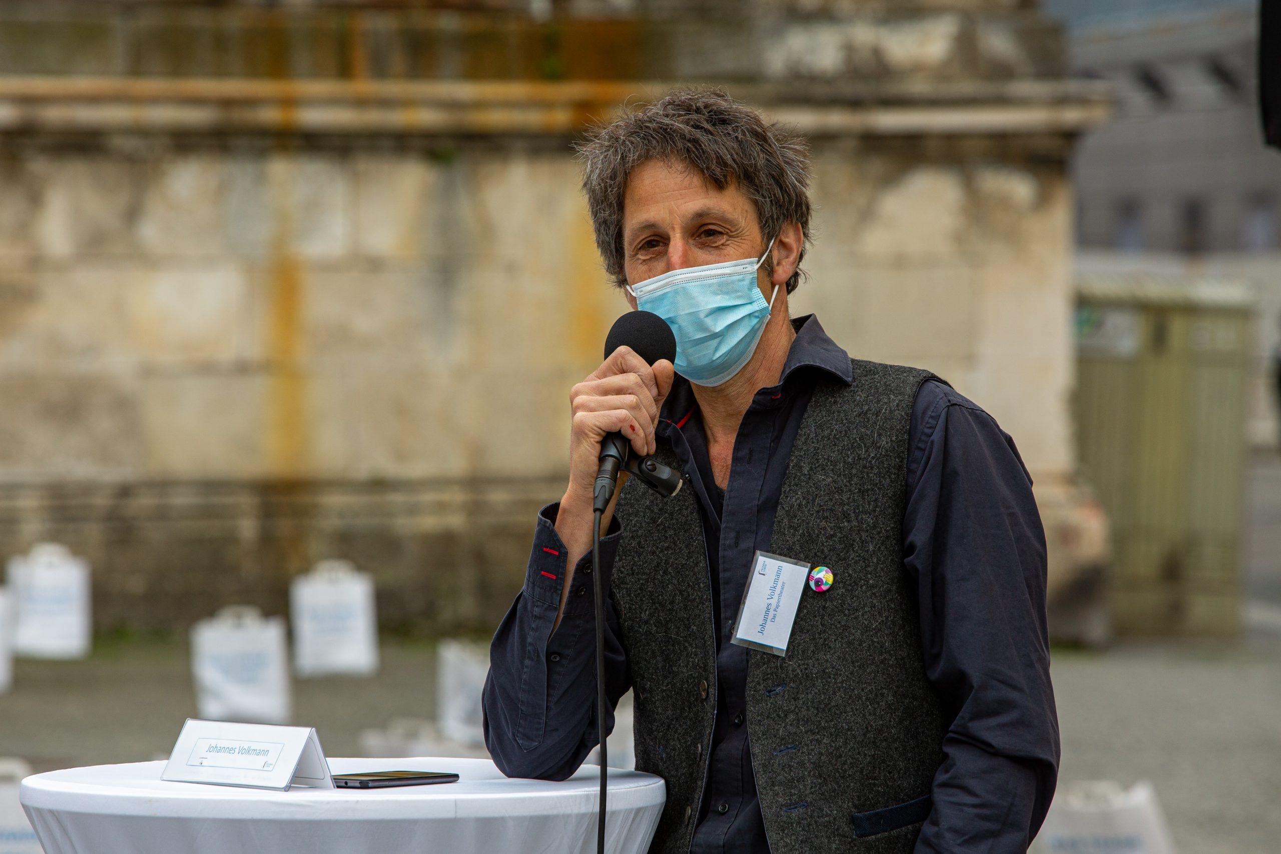 """Ein Mann mit Mikrofon an einem Stehtisch. Im Hintergrund Papiertüten bedruckt mit der Frage """"Was trage ich bei? Für eine friedliche Welt?"""