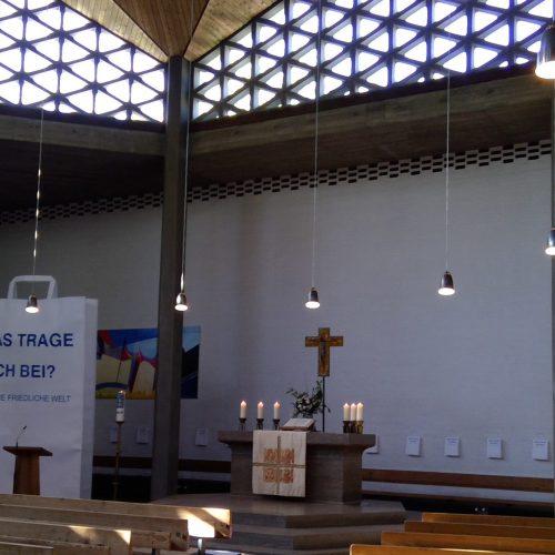 Eine riesige Papiertüte bedruckt mit der Frage Was trage ich bei? Für eine friedliche Welt in einer Kirche.