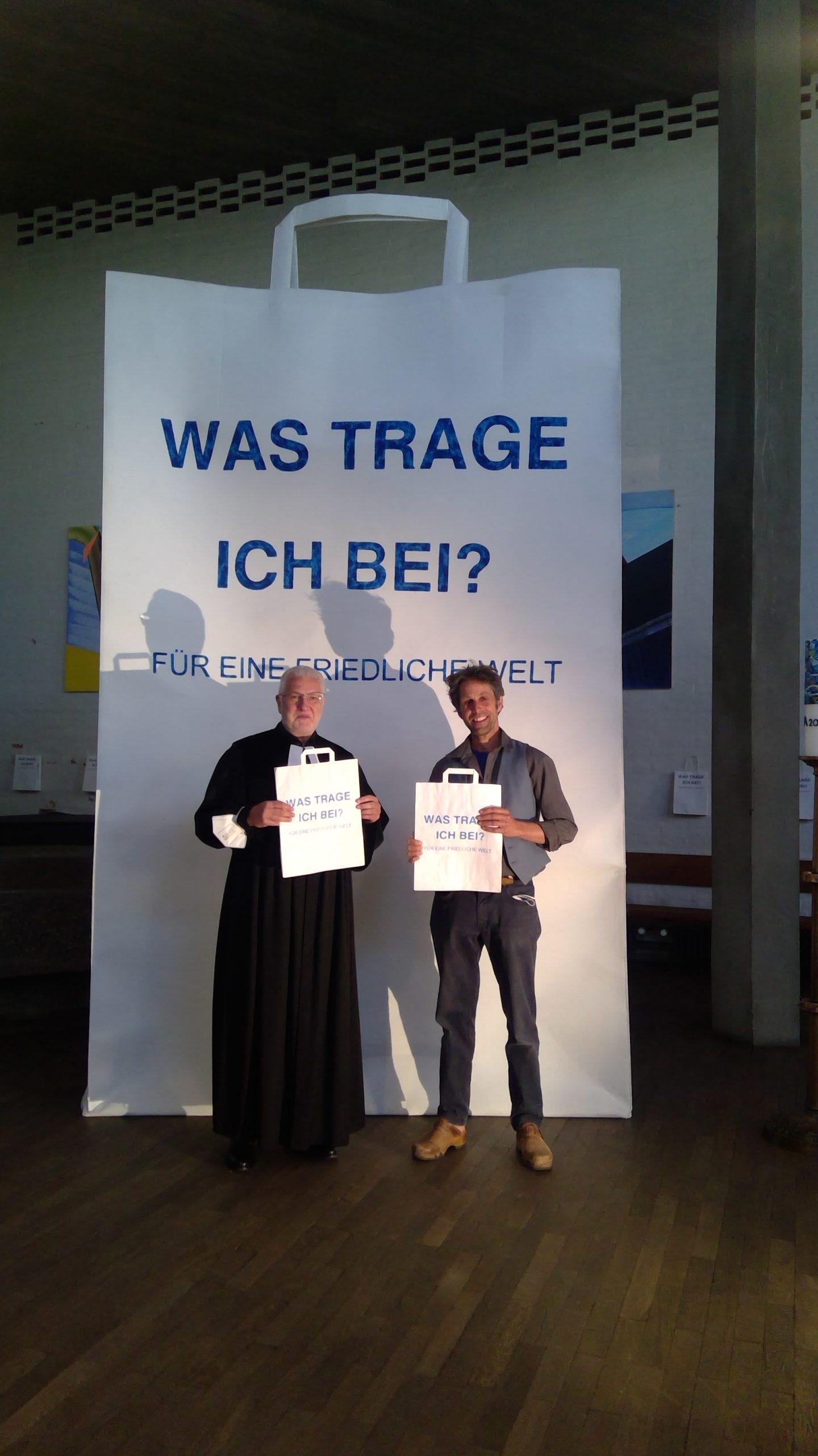 Eine riesige Papiertüte Was trage ich bei? Für eine friedliche Welt im HIntergrund. Davor stehen zwei Männer. Links ein Pfarrer, rechts ein Mann mit blauer Kleidung. Beide haben eine Papiertüte in der Hand.