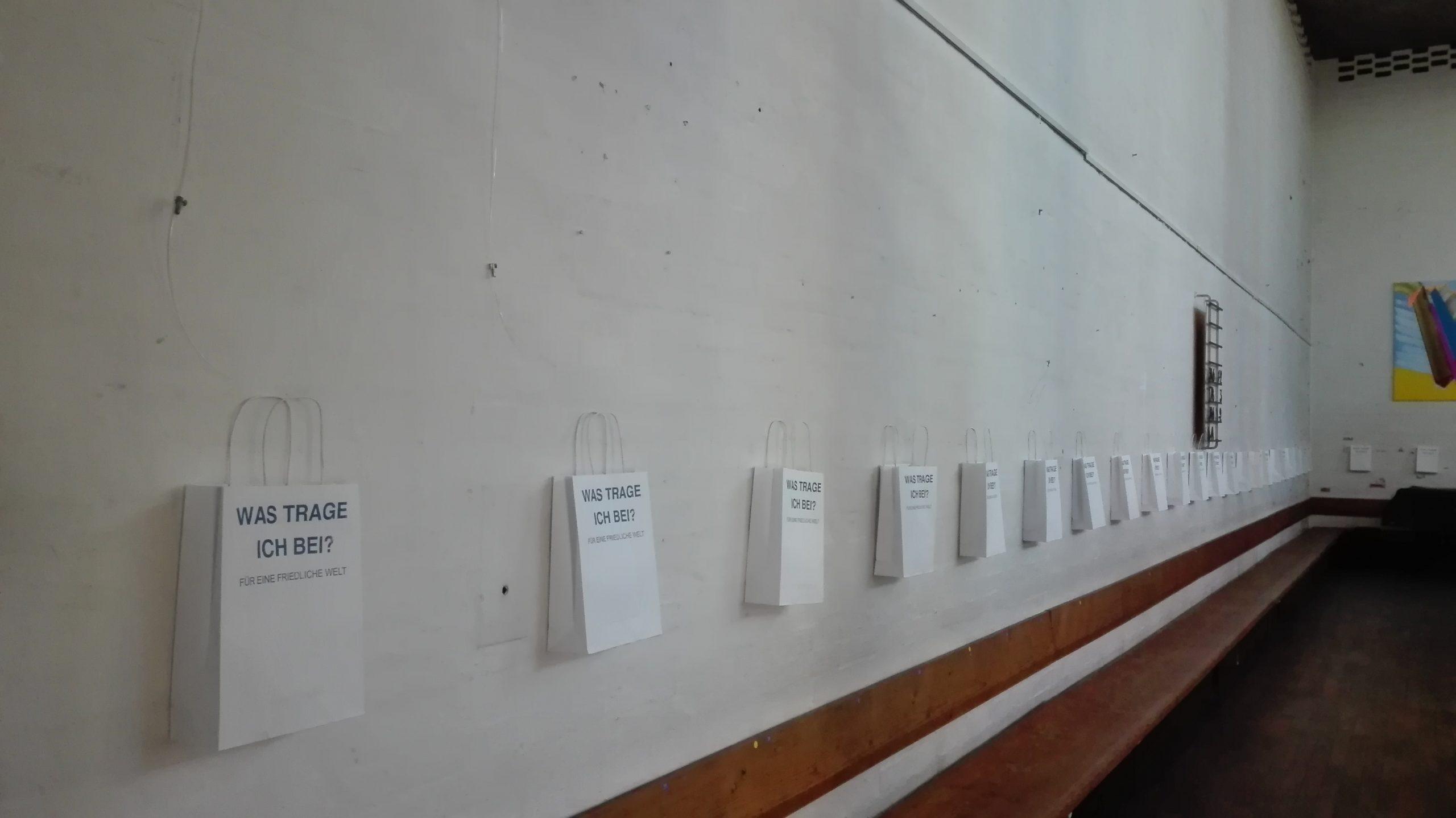 Kleine Papiertüten aufgereiht an einer Wand. Alle Tüten sind bedruckt mit der Frage Was trage ich bei? Für eine friedliche Welt.