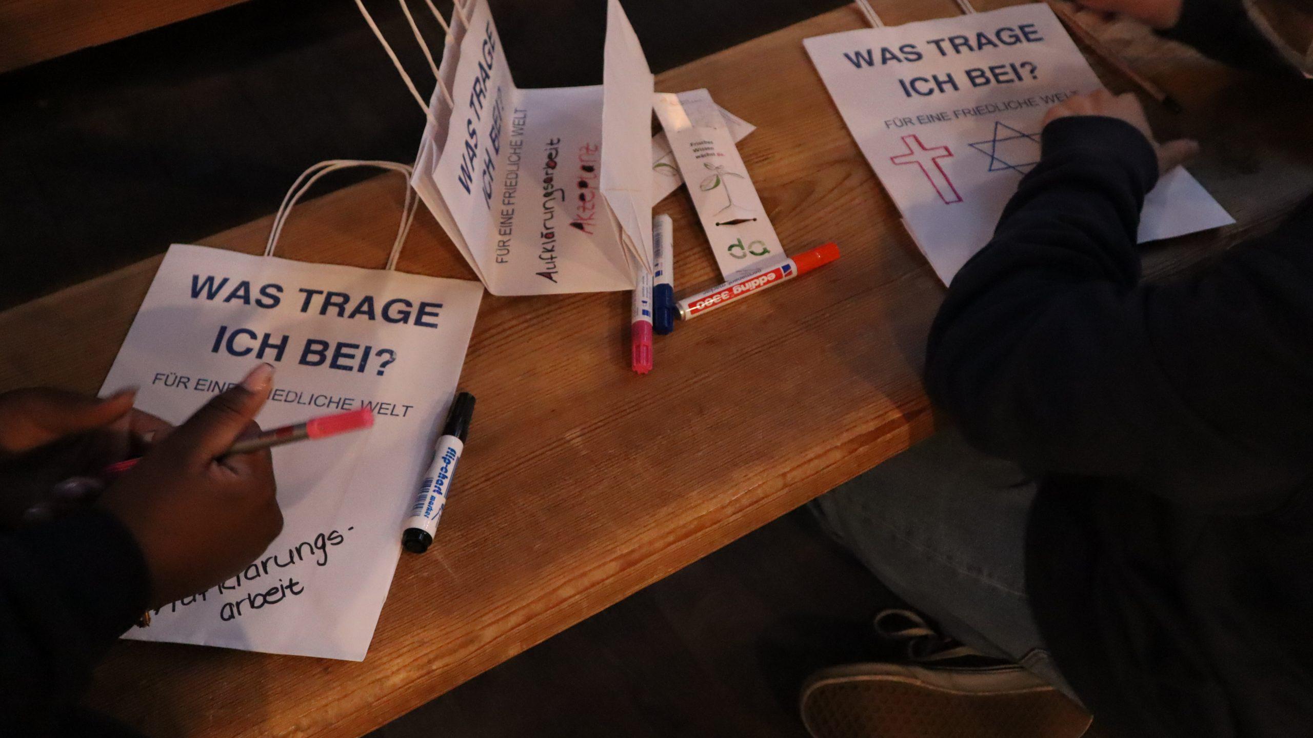 Weißee Papiertüten werden mit Stiften bunt bemalt.