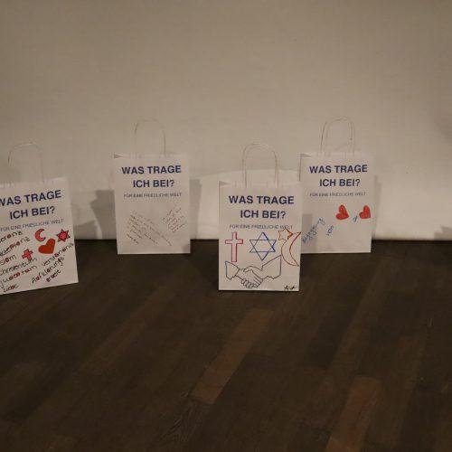 Kleine Papiertüten individuell mit Antworten auf die Frage Was trage ich bei? Für eine friedliche Welt stehen vor der großen Tütenskulptur.