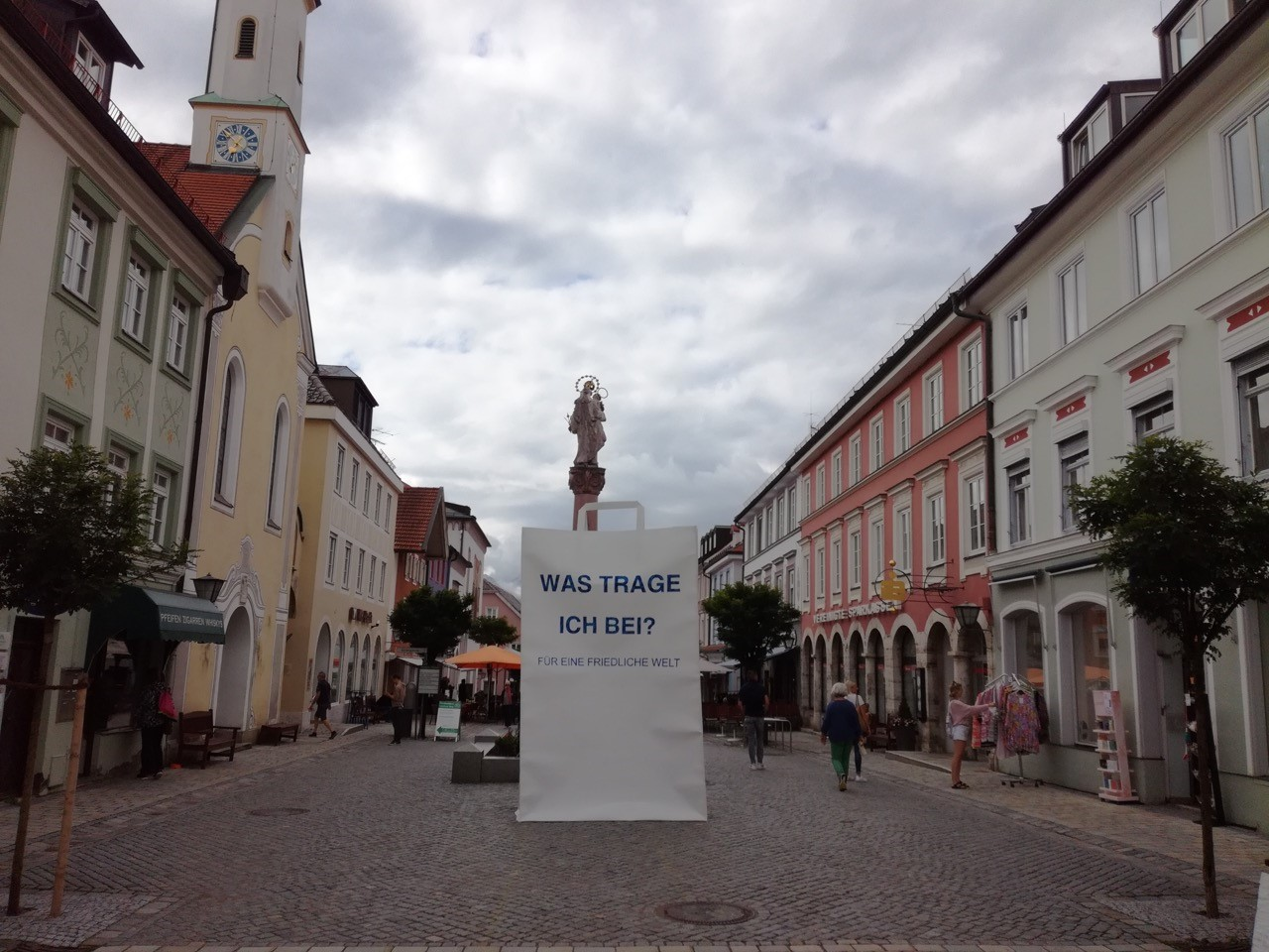 Eine 3,5m hohe Papiertüte steht mitten in der Altstadt von Murnau am Staffelsee. Im Hintergrund ist ein Brunnen und eine Kirche zu sehen.