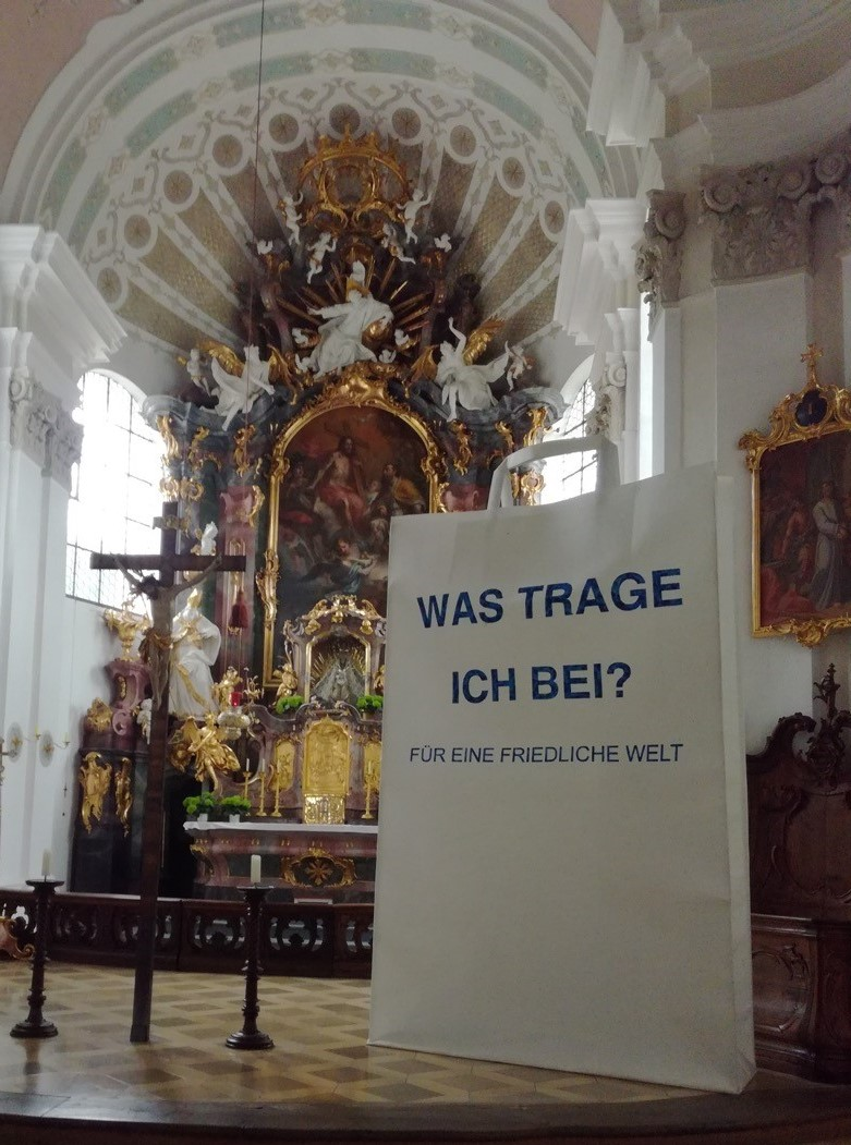 Eine 3,5m hohe Papiertüte steht in einer Kirche neben einem barocken Altar.
