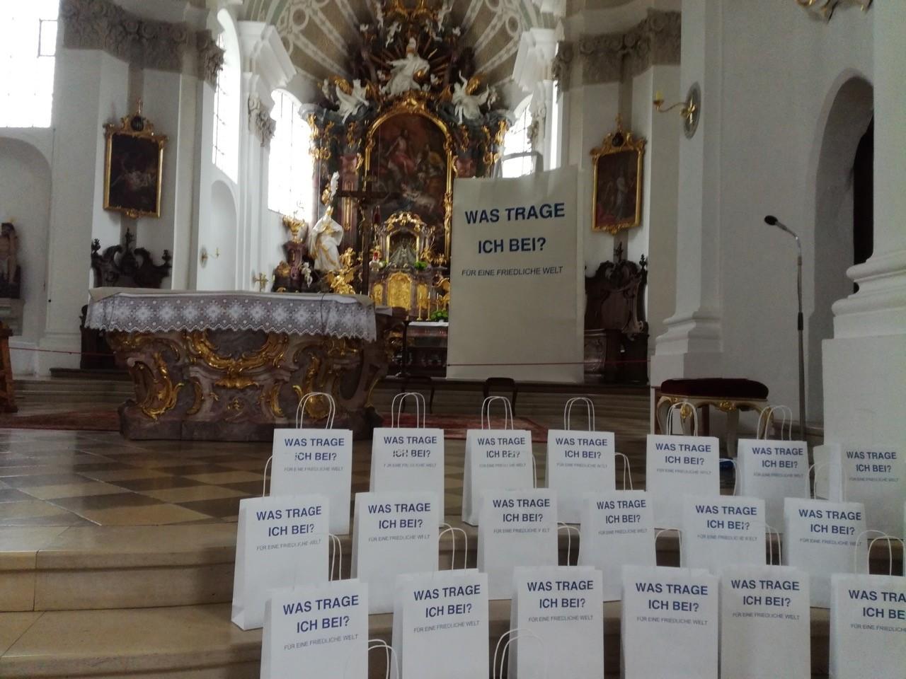 Eine 3,5m hohe Papiertüte steht gemeinsam mit kleinen aufgereihten Papiertüten in einer Kirche neben einem barocken Altar.