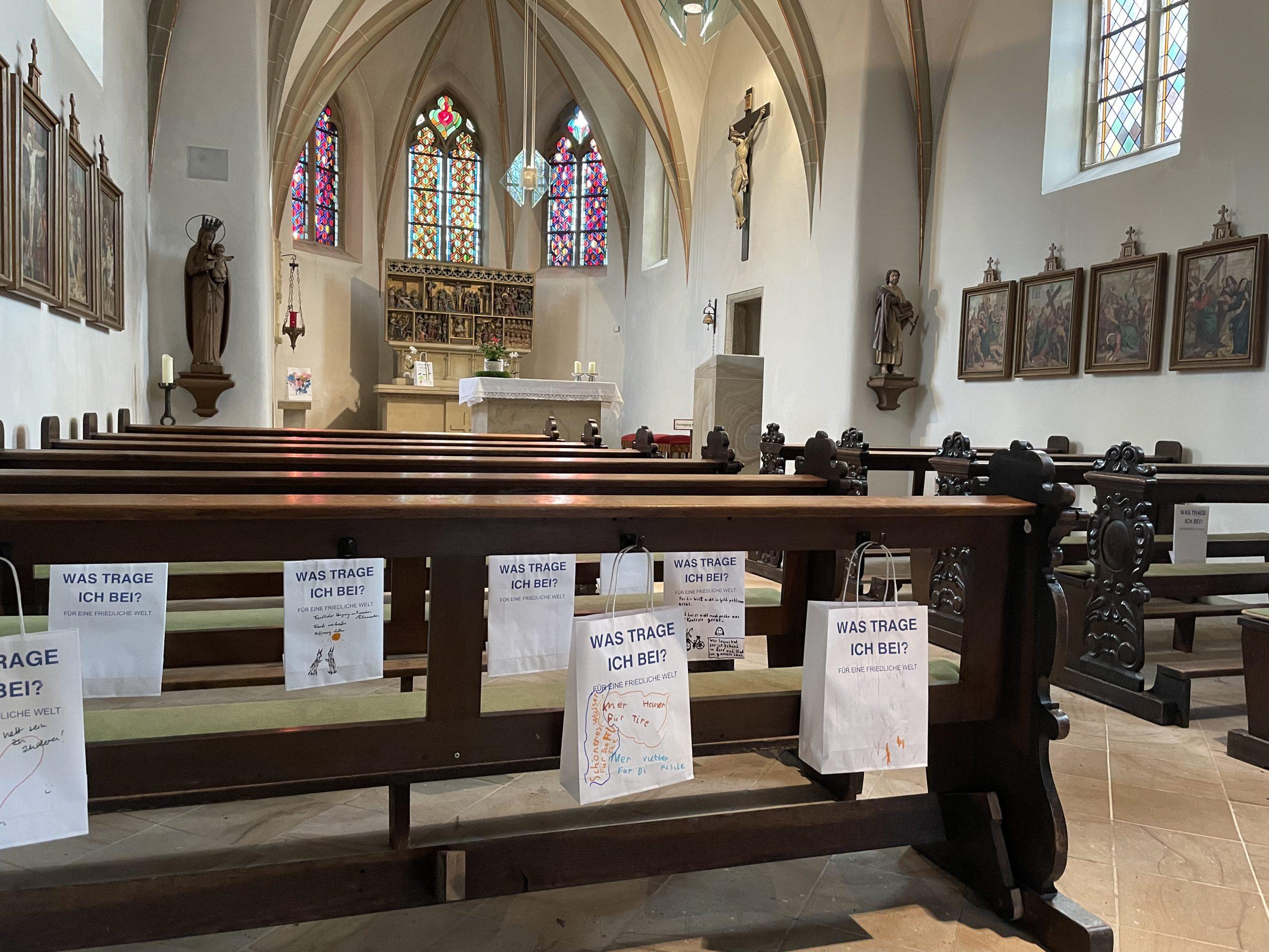 Innenraum einer Kirche mit Altar und Kirchenbänke. An den Bänken hängen buntbemalte Papiertüten des Friedens.