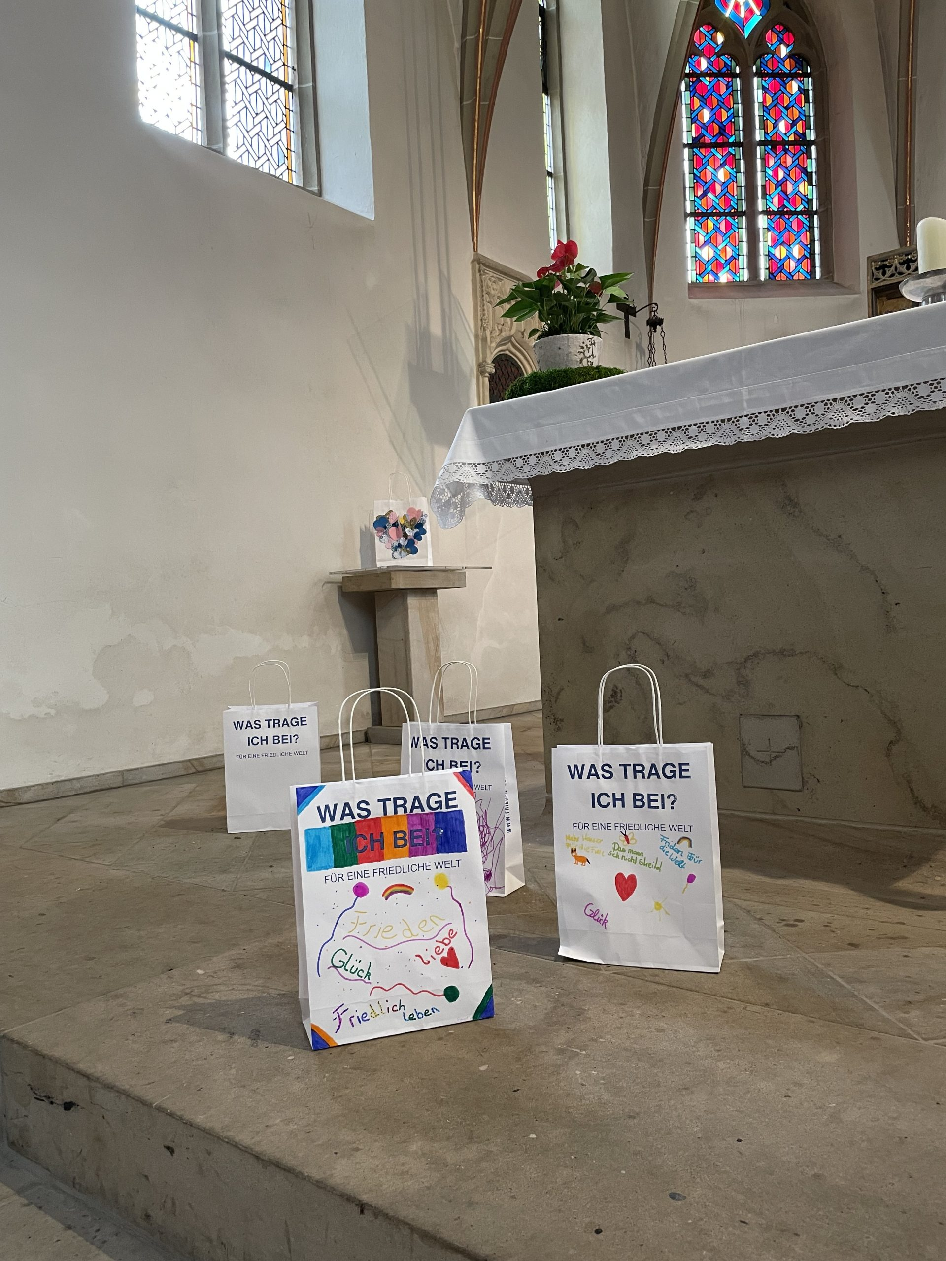 Auf einem Steinboden in einer Kirche stehen vier gestaltete Papiertüten mit Ideen für eine friedliche Welt.