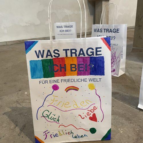 buntgestaltete Papiertüte des Friedens, beschrieben mit Glück, Firden, Liebe, friedliches Leben und Regenbogenfarben.