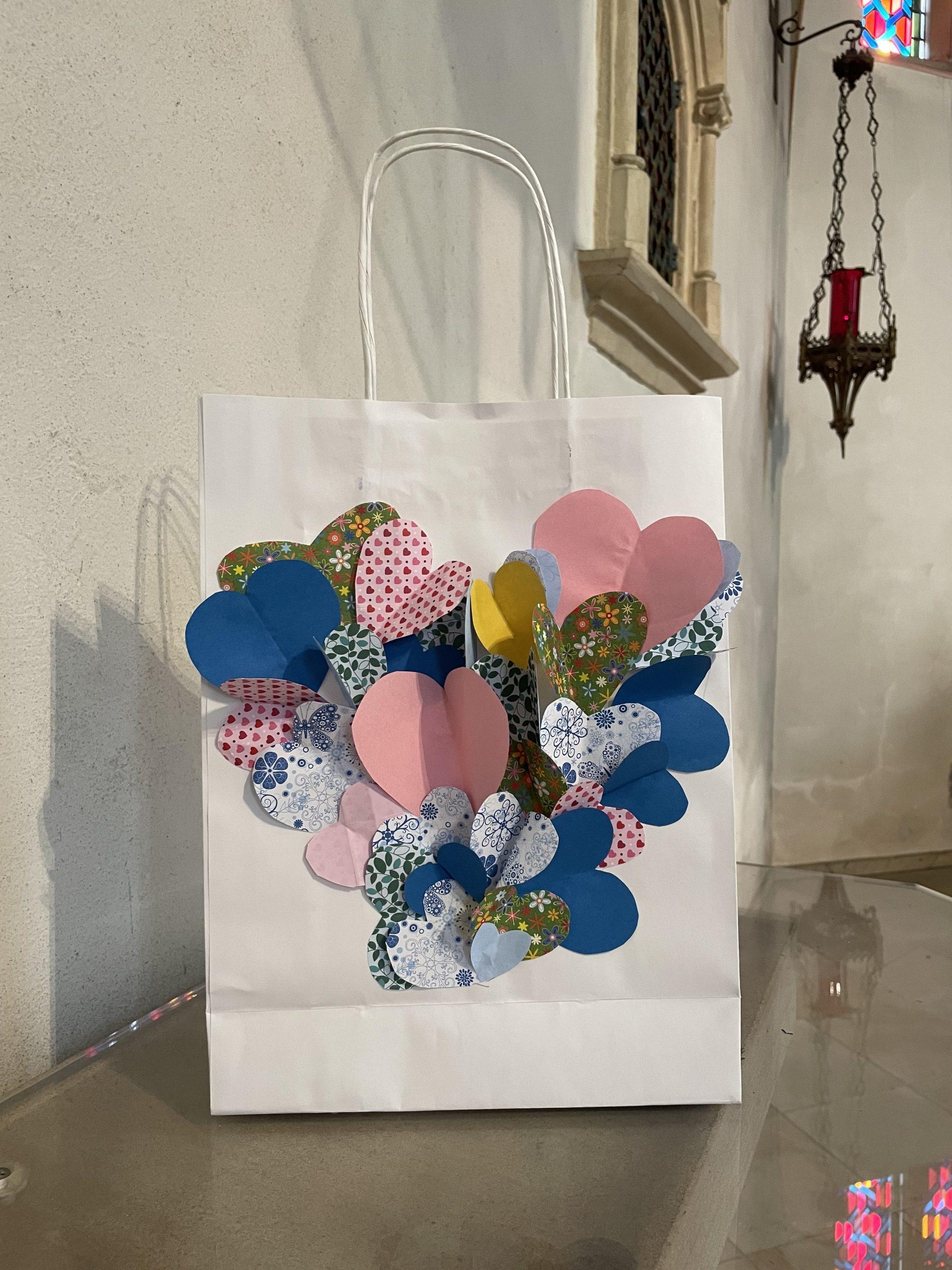 Eine Papiertüte des Friedens gestaltet mit gefalteten Herzen, die wie Schmetterlinge zu einem großen Herz zusammen geklebt sind.