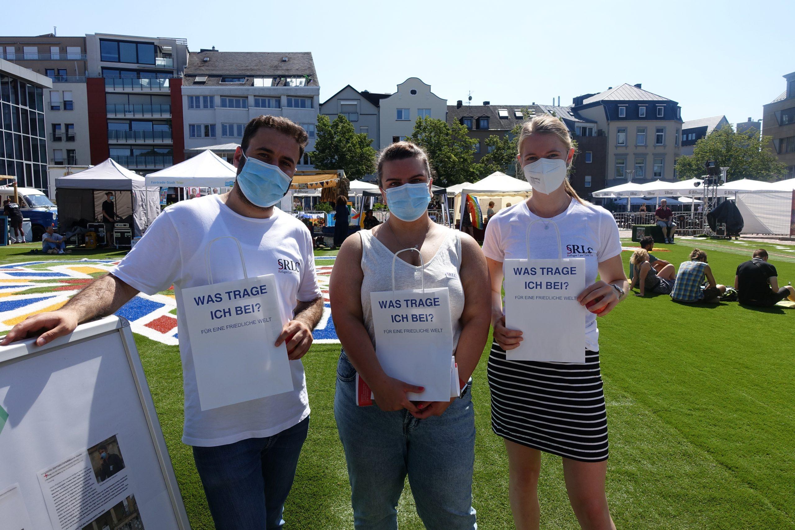 Drei Menschen mit Mundschutz halten eine Papiertüte des Friedens in der Hand.